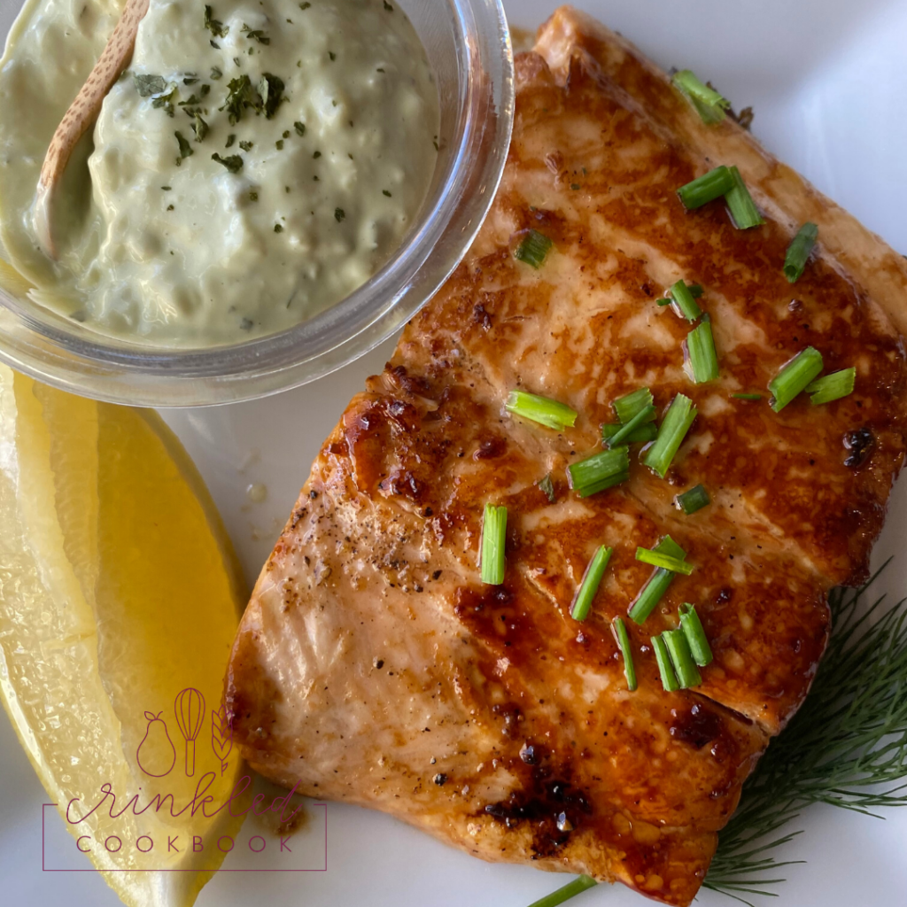 Skillet-glazed salmon on a plate with lemon and a dish of tarter sauce.