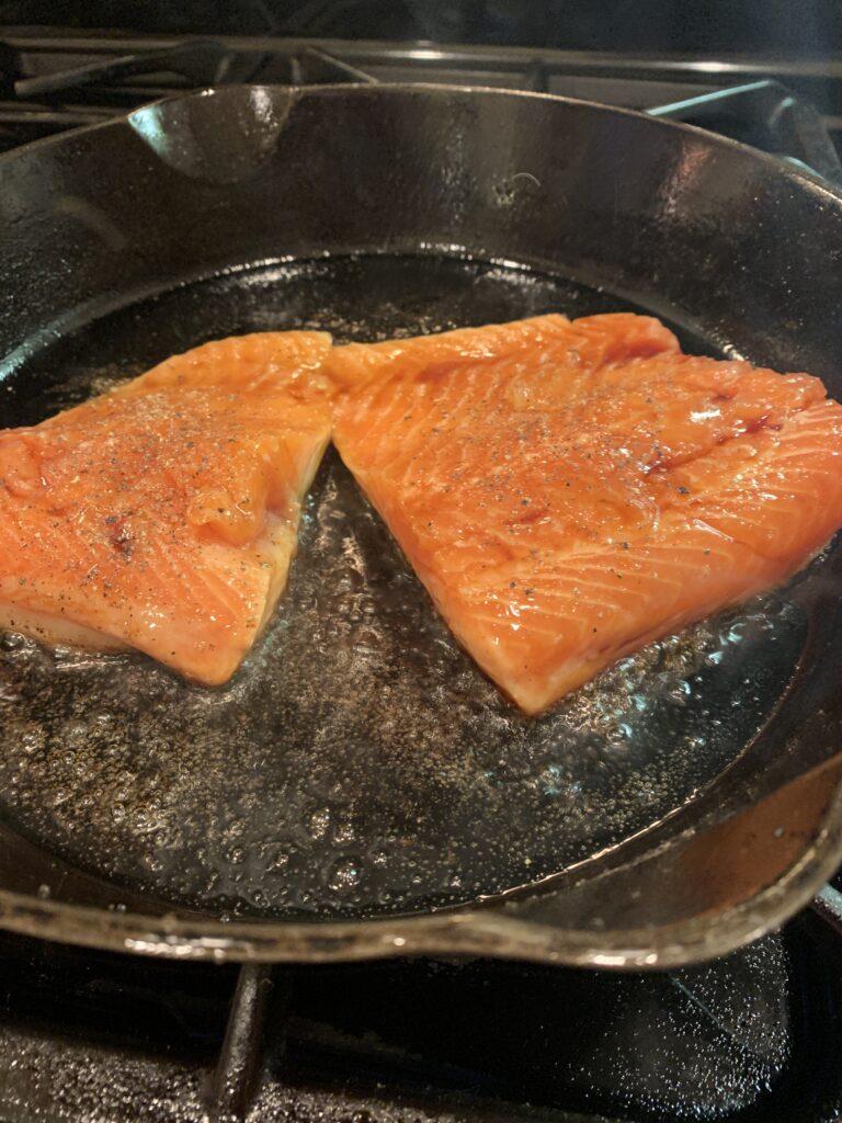 Salmon, skin side down in the skillet.