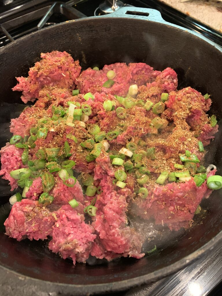 Ground beef and green onions in a skillet.