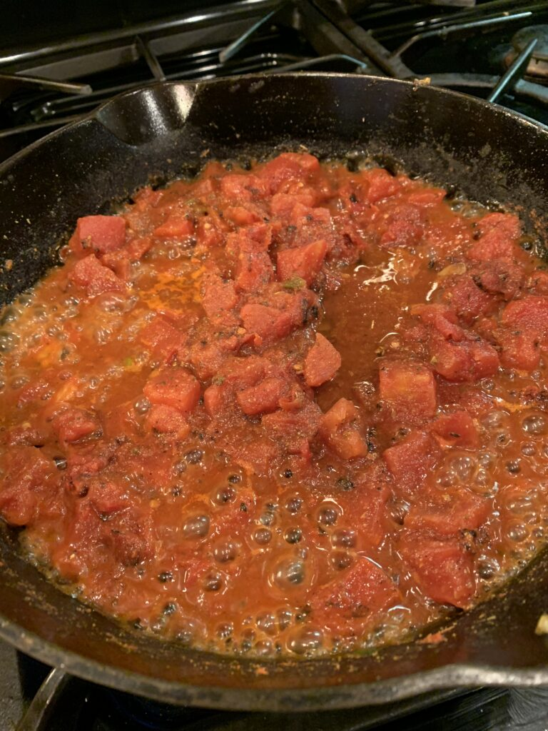 Tomato sauce simmering in a skillet.