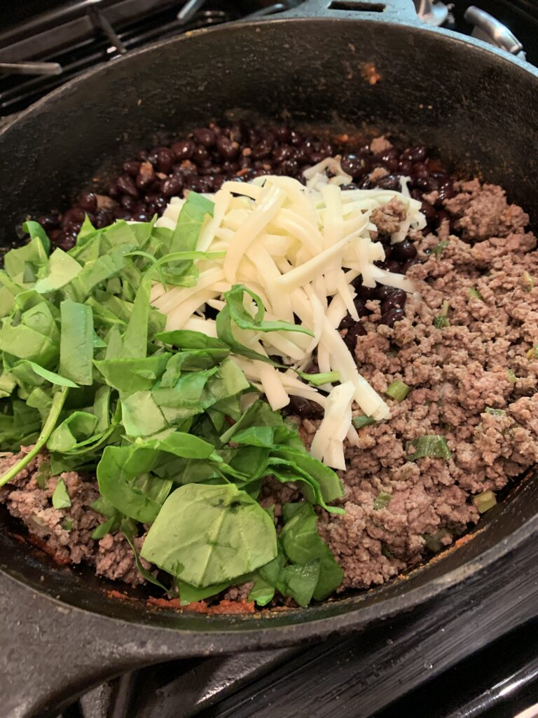 All the ingredients for beef baked burrito filling arranged in a skillet.