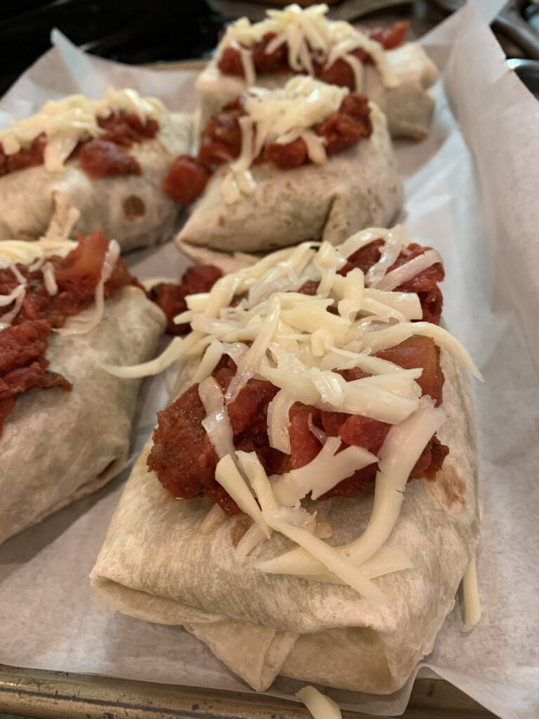 Burritos covered with tomato sauce and cheese on a baking dish.