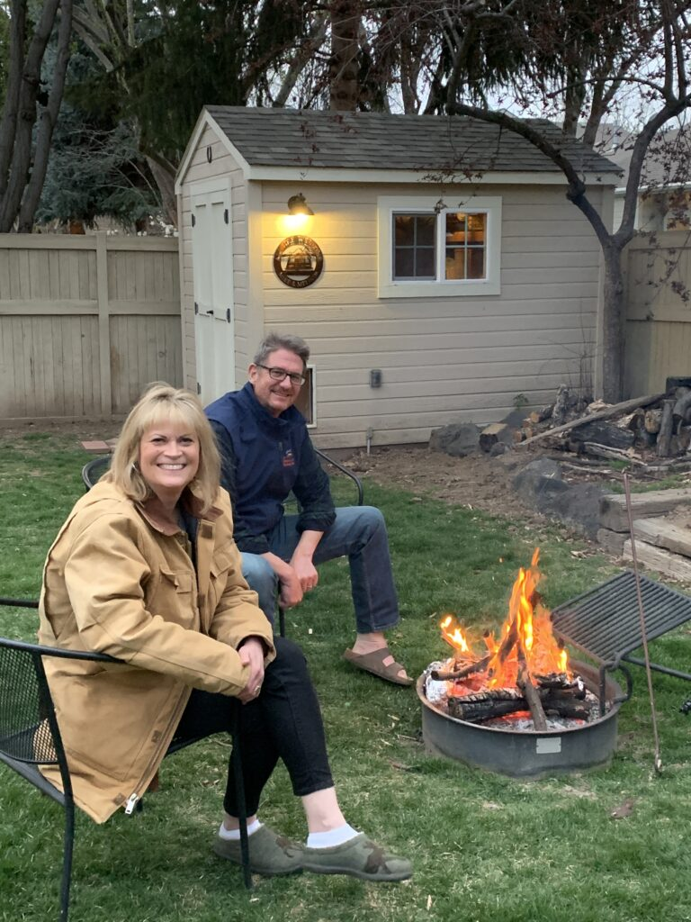 Melinda and her husband in their backyard, but a fire pit.