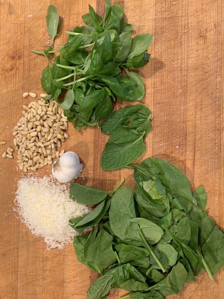 Basil, mint and spinach with garlic and pine nuts and parmesan on a cutting board.