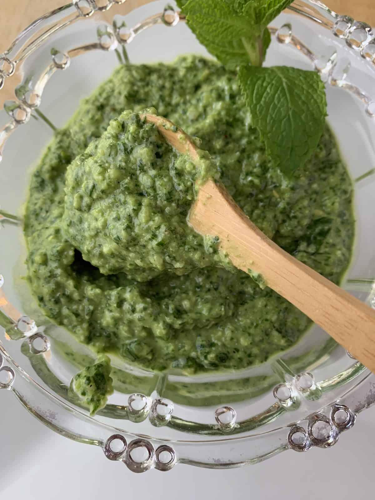 Pesto sauce in spoon over a bowl of pesto