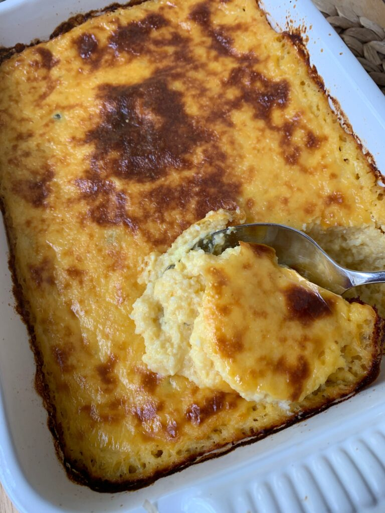 Baked cheesy chili grits in a dish.
