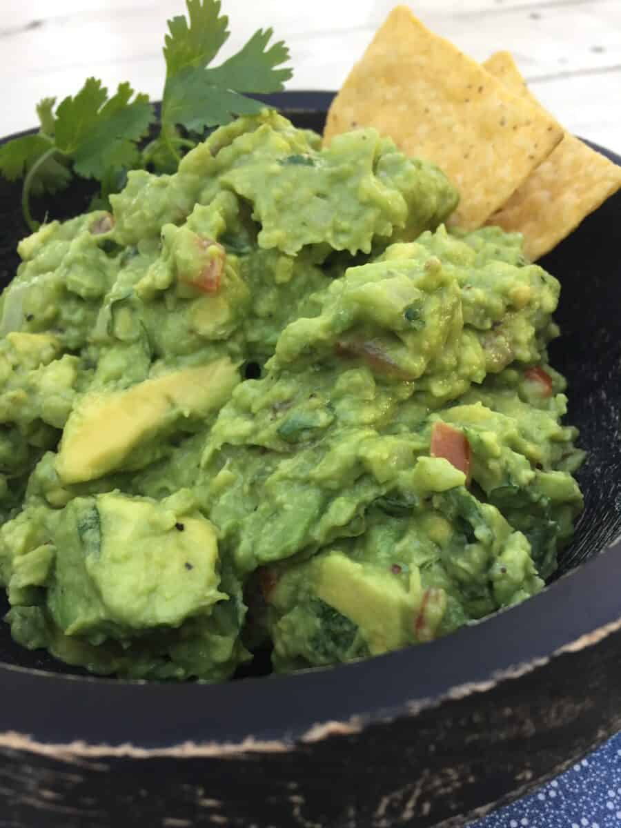 Guacamole in a bowl with chips.