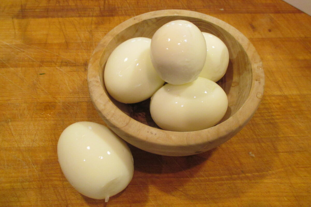 Hard boiled eggs in wooden bowl.