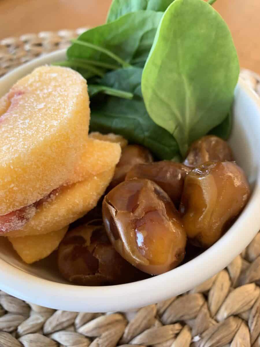 Peaches, dates and spinach in a small bowl.