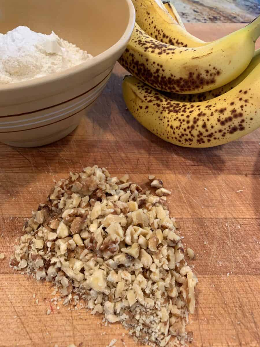 Chopped walnuts, ripe bananas and a bowl on a cutting board.