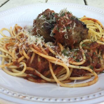 Meatballs on top spaghetti and sauce, with cheese garnish.