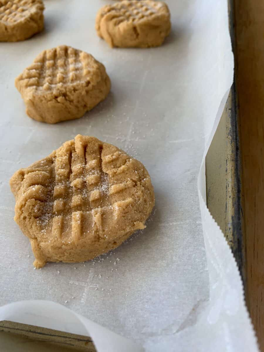Peanut butter cookies on a baking sheet, with a criss cross pattern in the dough.