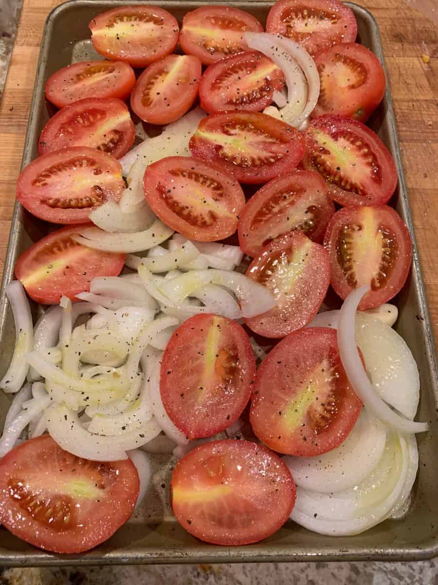 Tomatoes, garlic and onions chopped and arranged on a baking sheet.