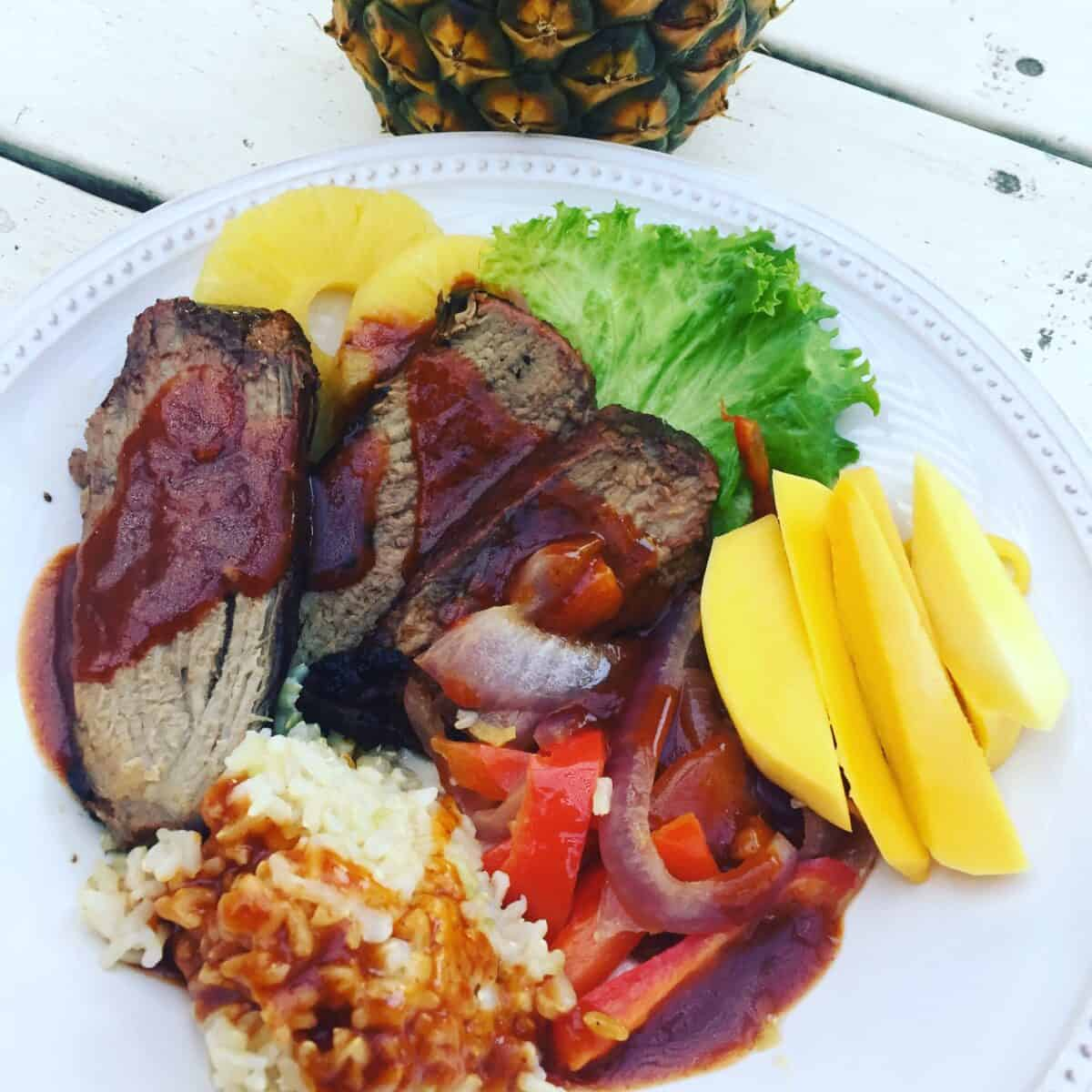 Idaho beef on a plate with rice, mango, red onion, red pepper, pineapple and lettuce.