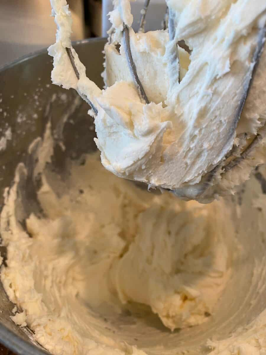 Buttercream frosting in the mixing bowl and on a whisk.