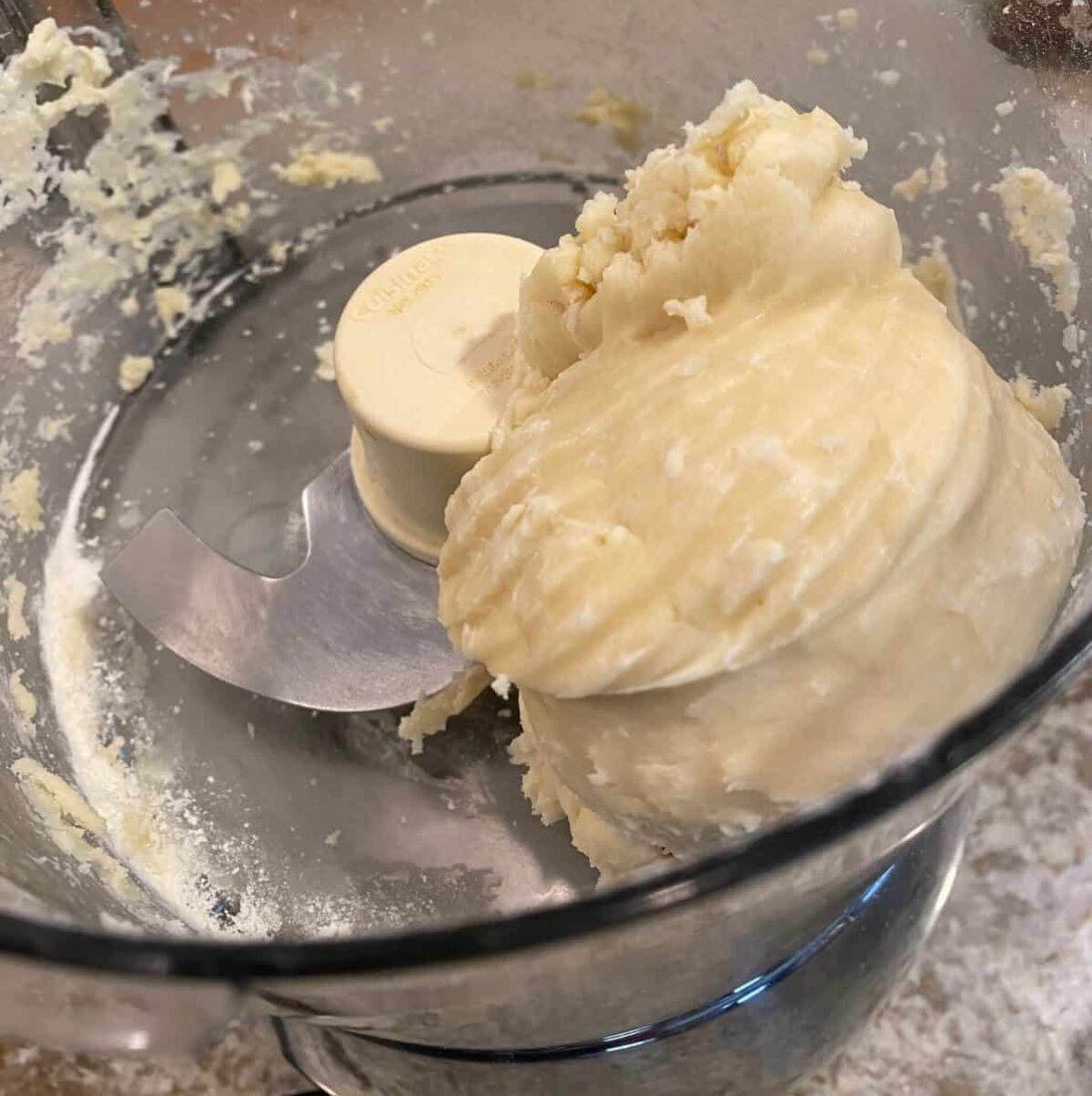 Small mound of unbaked shortbread dough in a food processor.