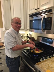 Melinda's dad frying cod in a cast iron skillet on the stove.
