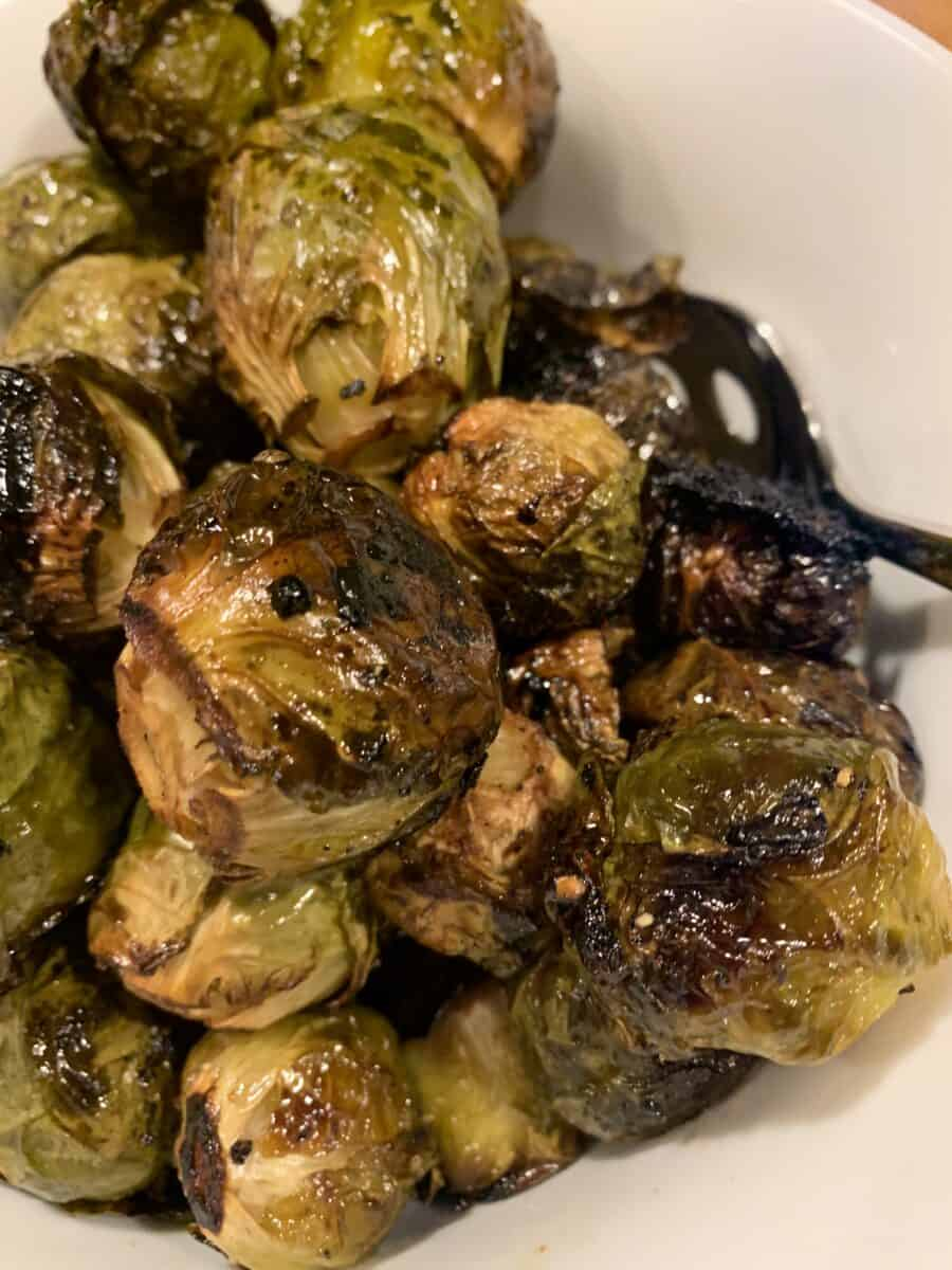 Whole, glazed Brussels sprouts on a serving bowl after roasting