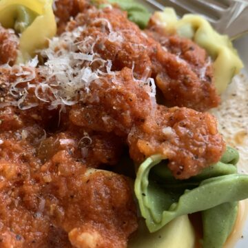 Tomato-cream sauce on top of plain and spinach tortellini.