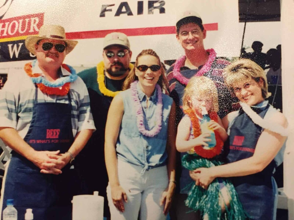 Six people in front of a banner at the Western Idaho Fair, 1999.