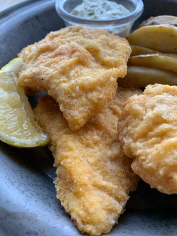 Three pieces of fried cod on a metal plate.
