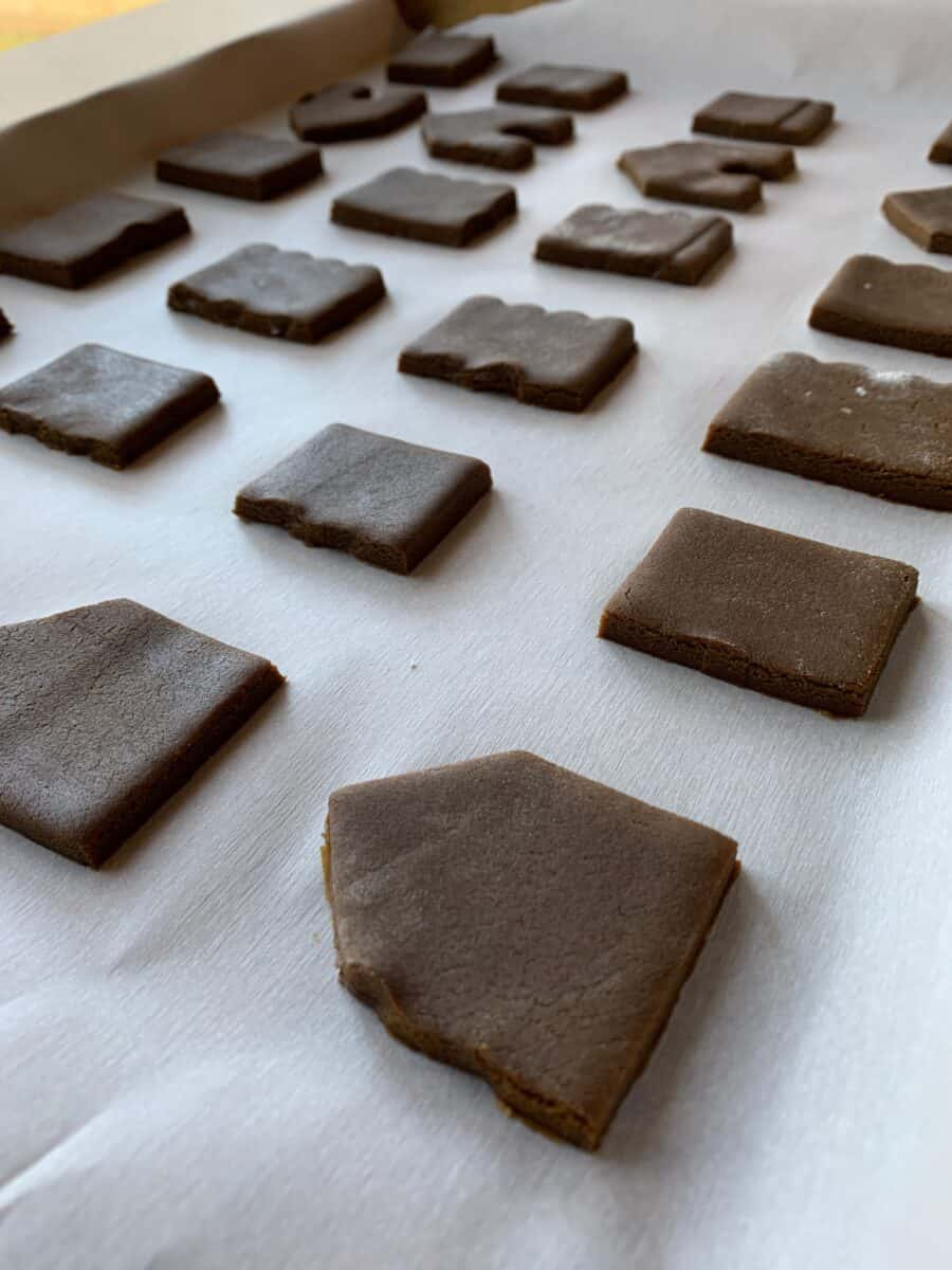Portions of the mini-gingerbread house on a baking sheet, ready to bake.