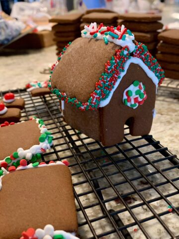 Mini-gingerbread house, decorated with icing, on a cooling rack