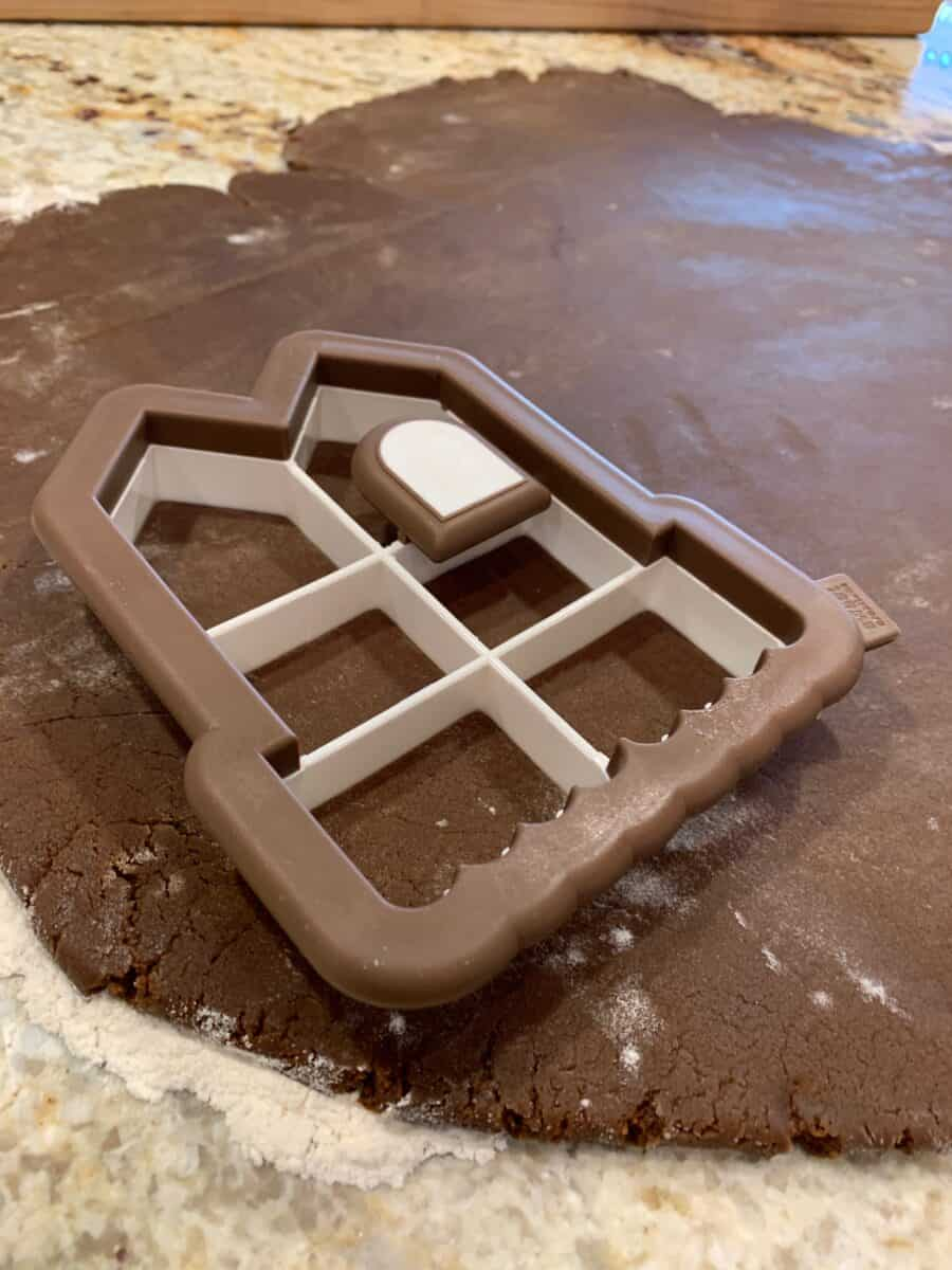 Cookie cutter placed on a rolled sheet of gingerbread dough.