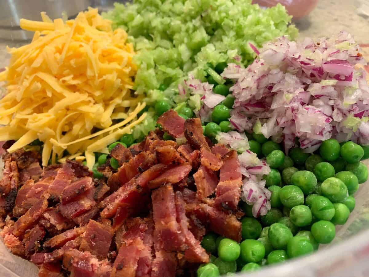 Pea salad ingredients: bacon, cheese, celery, bacon and red onions.