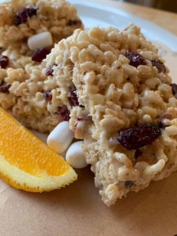 Rice Krispie treats stacked with a wedge of orange on the side.