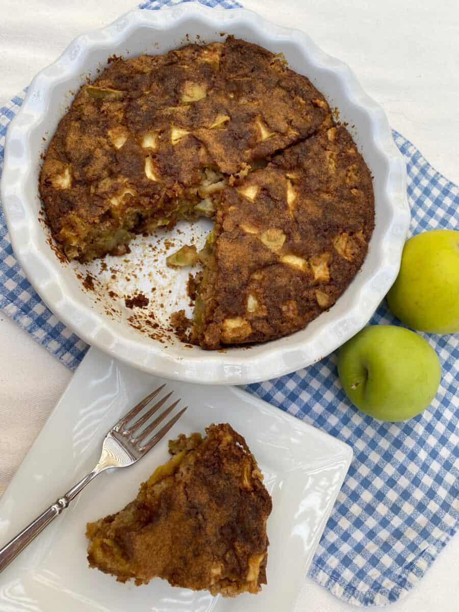 A wedge of apple cake with the baking dish and and apples in the background.