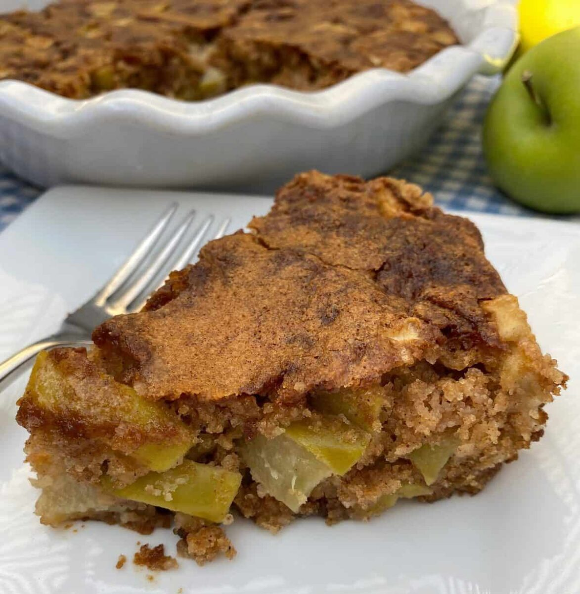 A wedge of apple cake with the baking dish and an apple in the background.