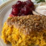 Cookie Crumb Casserole scooped onto a plate with cranberries, chicken and a sprig of rosemary.