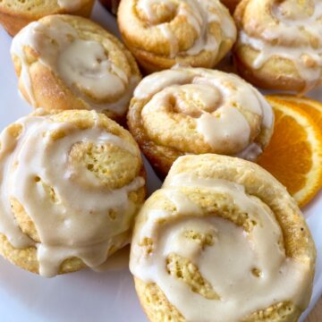 Orange sweet rolls arranged on a serving dish with a slice of orange.
