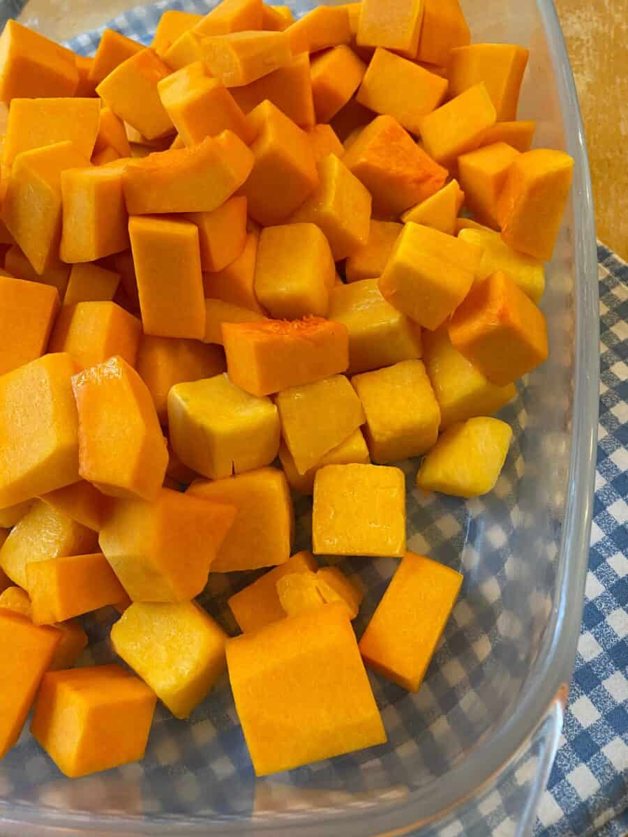 Diced butternut squash spread out in a glass baking dish on a placemat.
