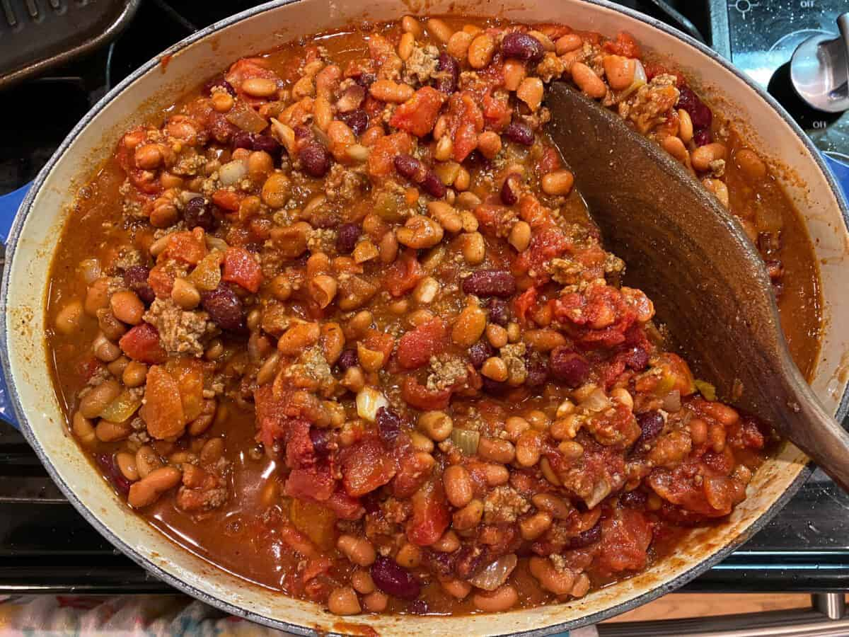 A large pot of chili on the stove with a wooden serving spoon.