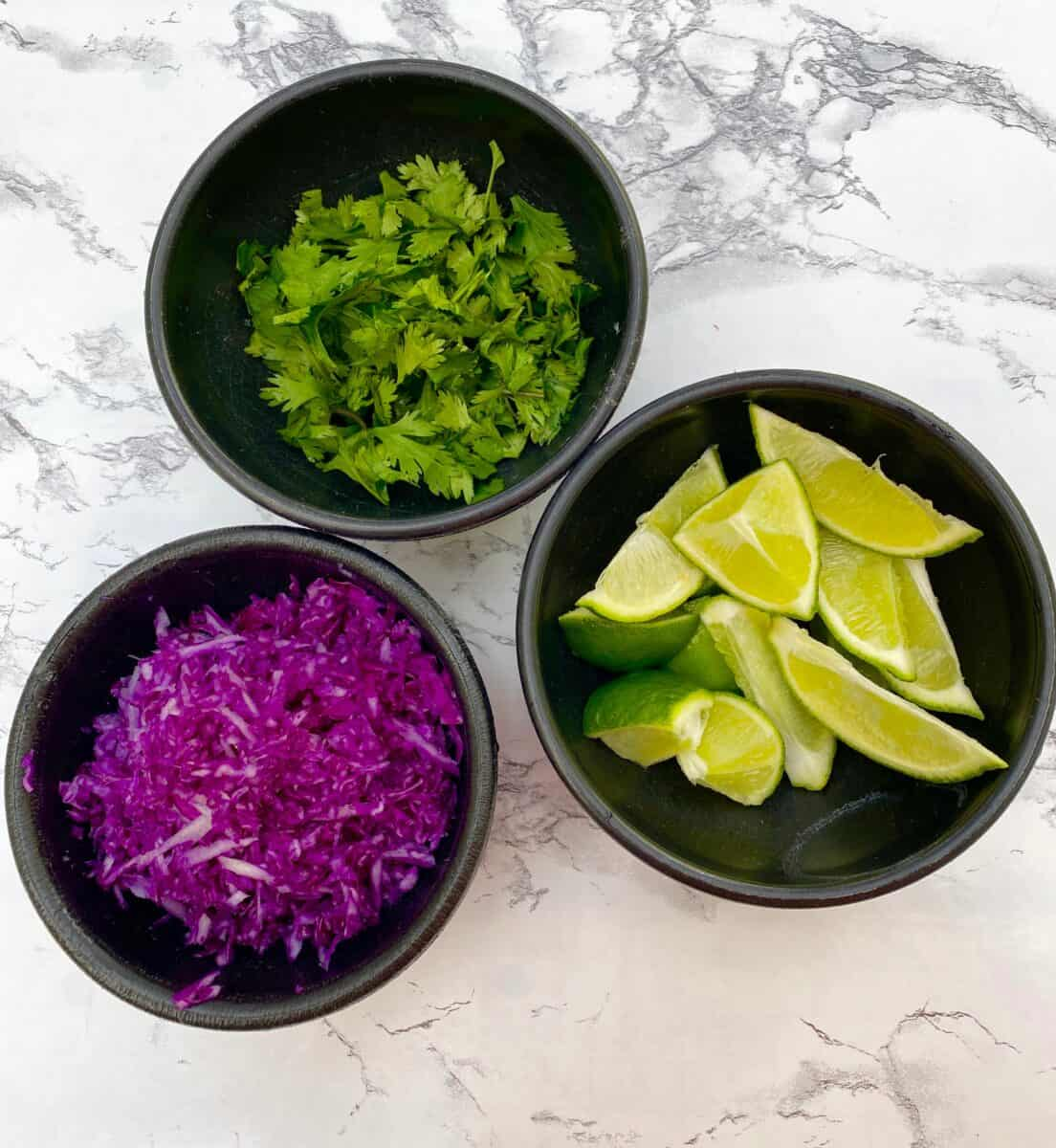 Red cabbage, limes and cilantro in small bowls on a counter.