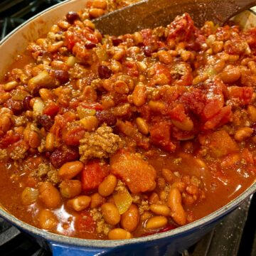 A large stockpot on the stove full of chili.