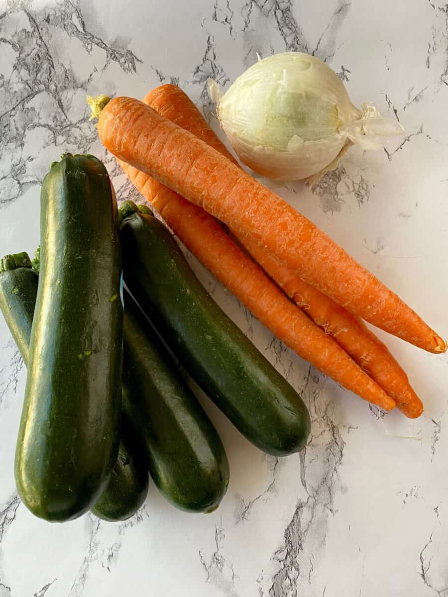 Four zucchinis, three carrots and an onion on a counter.