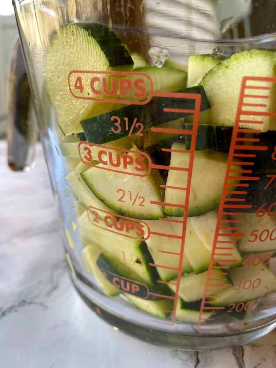 Diced zucchini in a 4-cup glass measuring cup.