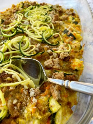 Baking dish with zucchini casserole and a serving spoon.