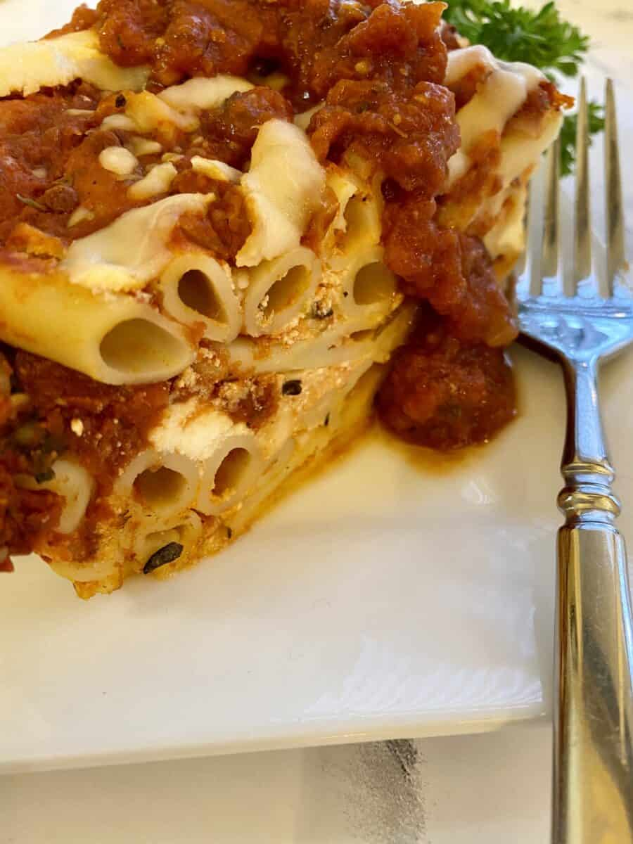 Baked ziti on a plate with sauce on the top and a fork on the side.