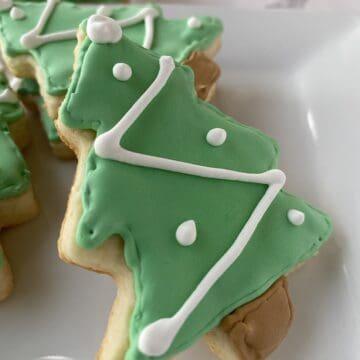Sugar cookies shaped like Christmas trees on a plate.