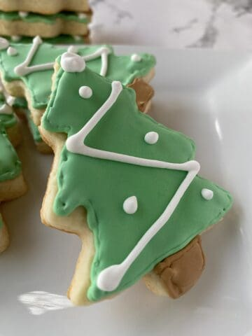 Sugar cookies shaped like Christmas trees on a plate.