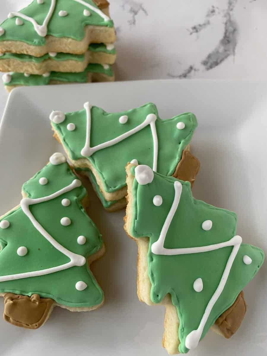 Sugar cookies shaped like Christmas trees stacked and arranged on a plate.