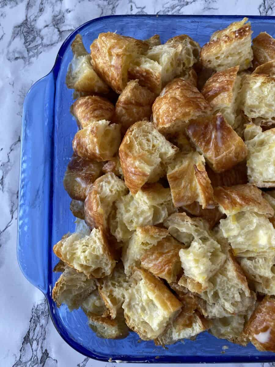 Diced croissants in a glass baking dish.
