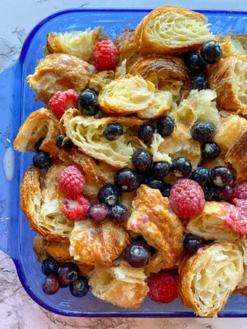 Croissant bread pudding with fruit in a baking dish, before baking.
