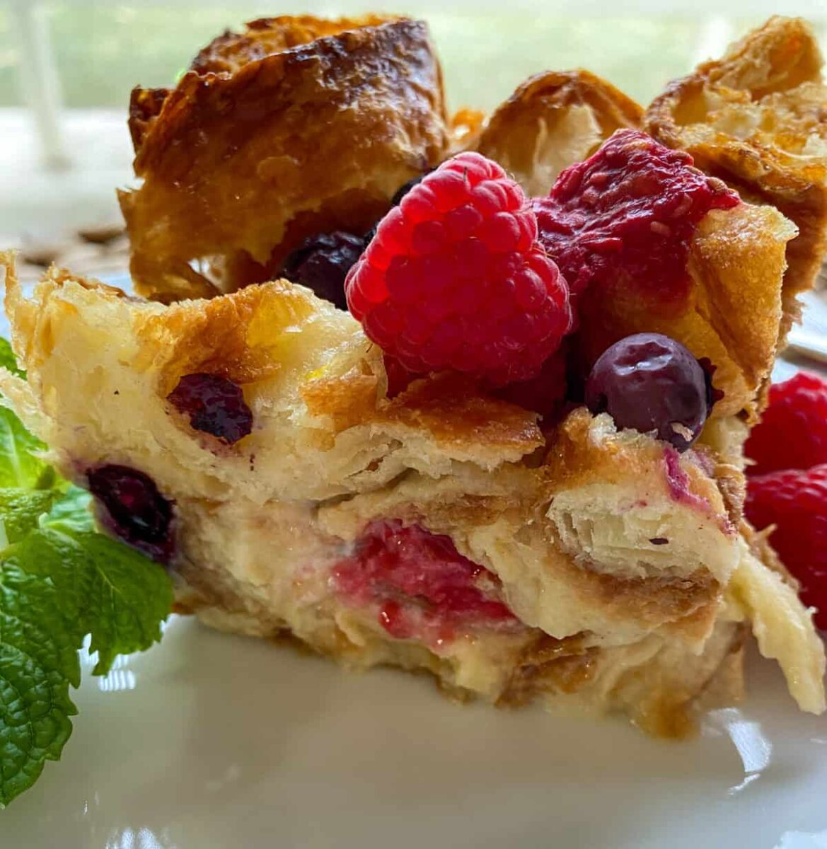 A portion of bread pudding on a plate with fresh raspberry on top.