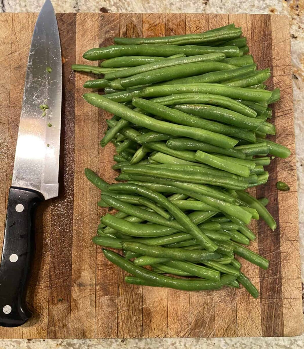 Green beans and a knife on a cutting board.