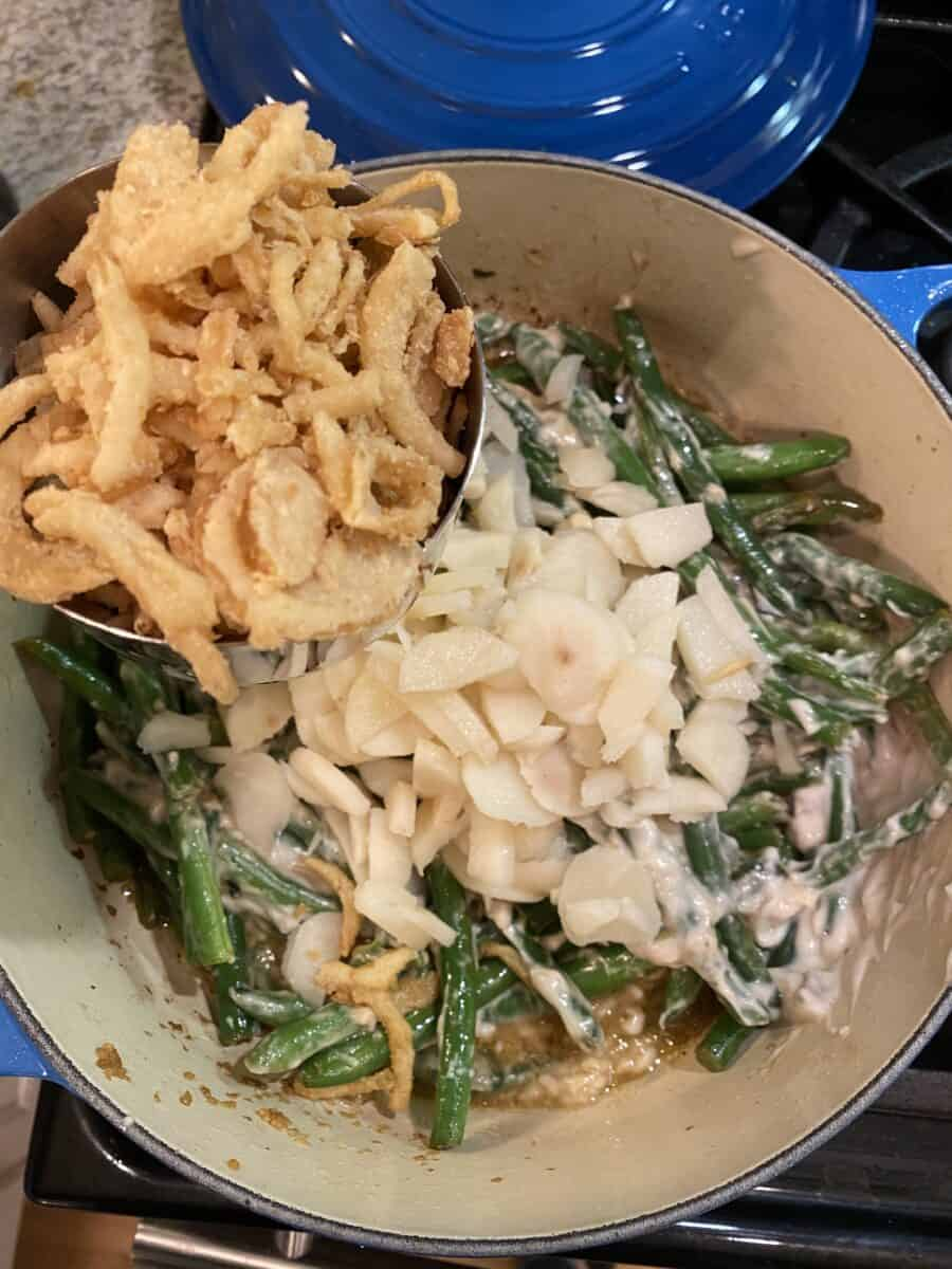 Green beans, water chestnuts and fried onions in a pan on the stove.